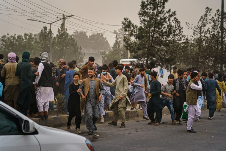 Image: Afghans run away after Taliban fighters use guns fire, whips, sticks and sharp objects to maintain crowd control over thousands of Afghans who continue to wait outside the Kabul Airport