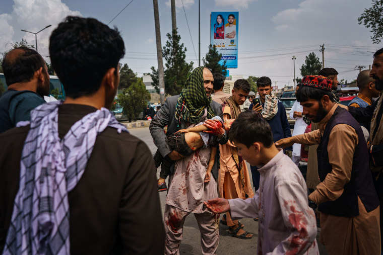 Image: A man carries a bloodied child on the street after Taliban fighters use guns fire, whips, sticks and sharp objects to maintain crowd control over thousands of Afghans who continue to wait outside the Kabul Airport