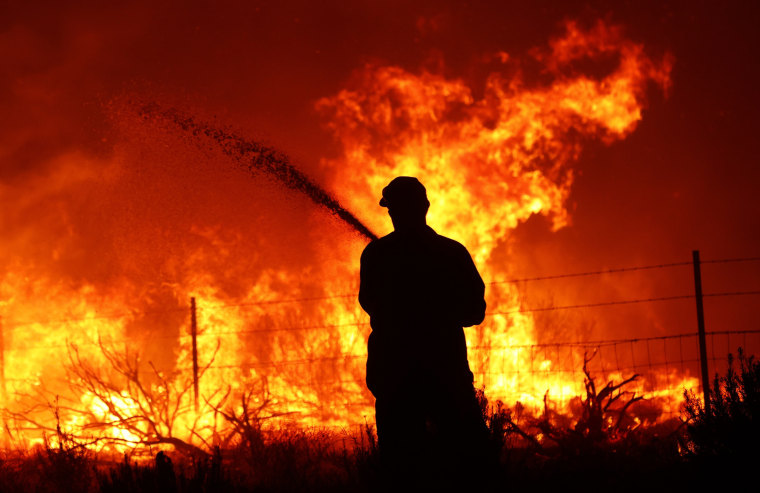 A utility worker uses a hose to extinguish fire near power poles as the Dixie Fire moves through the area on Aug. 16, 2021, near Janesville, Calif.