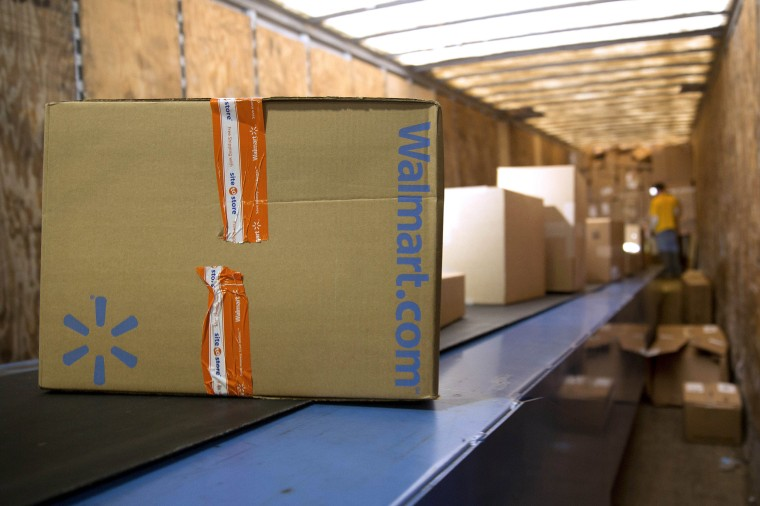 Image: A Wal-Mart Stores Inc. package is unloaded from a trailer to be sorted for final delivery at a FedEx Corp. Ground hub in Hagerstown, Md.
