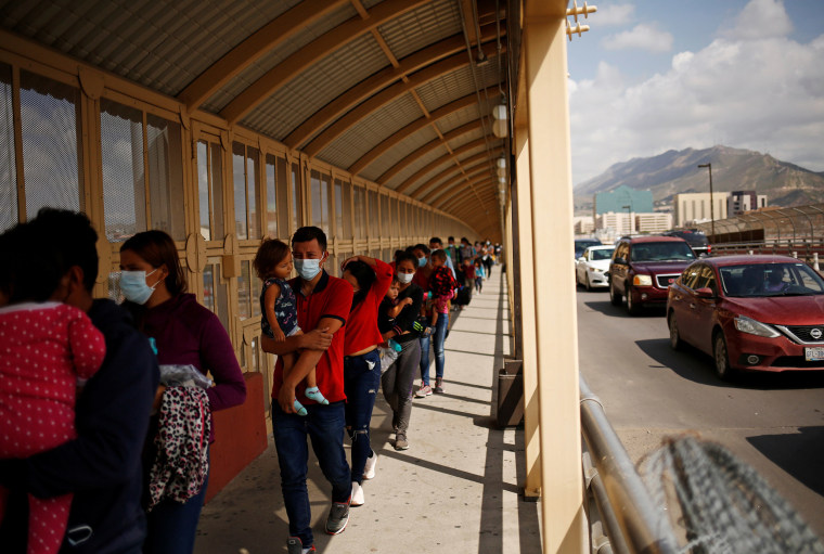 Image: Central American migrants expelled from the U.S. under Title 42 walk towards Mexico on the Lerdo Stanton International Bridge, as seen from Ciudad Juarez