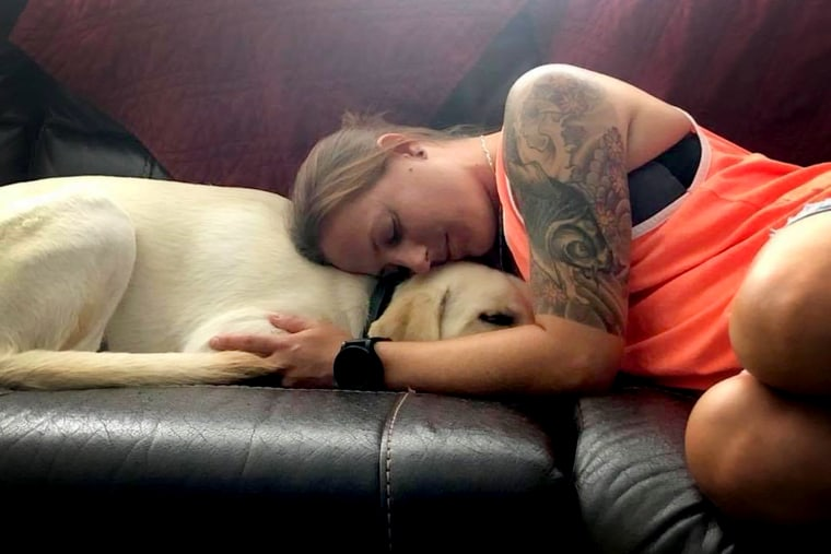Becca Stephens comforting — and being comforted by — her service dog, Bobbi.