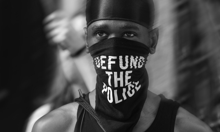 """Image: A Black trans liberation activist wears a bandana that reads \""""Defund the Police\"""" in New York City."""