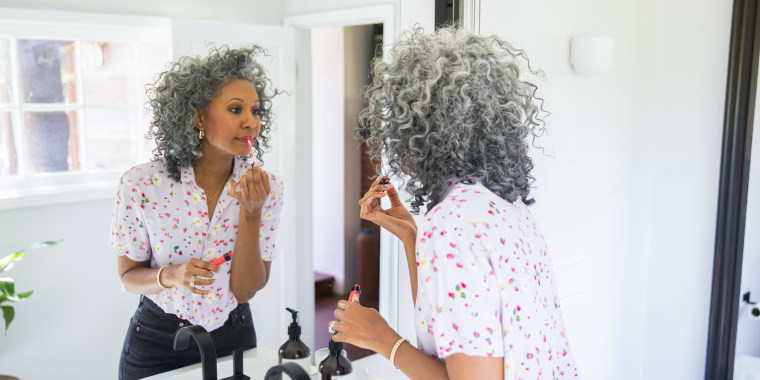 Beautiful Woman putting on her makeup in a bathroom mirror