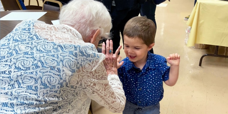 Benjamin Olson, 2, helps his best friend and neighbor Mary O'Neill celebrate her 100th birthday.