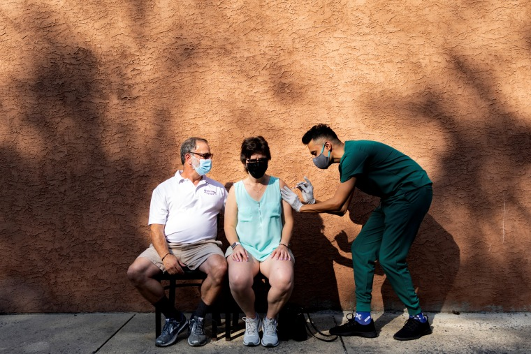 IMAGE: A woman receives a booster dose of the Pfizer-BioNTech Covid-19 vaccine at a pharmacy in Schwenksville, Pa., on Aug. 14, 2021.