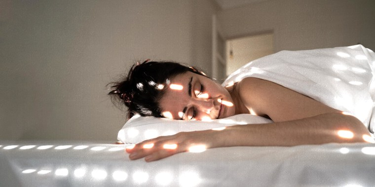 Woman Lying On Bed At Home, with light shining on her face