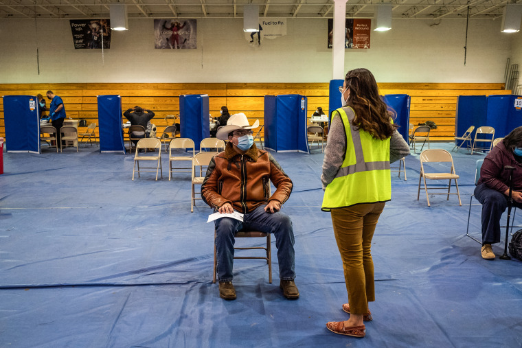 A volunteer, right, speaks with a person that received the Covid-19 vaccine in a waiting area in the gymnasium at the University of New Mexico's Gallup campus in Gallup, New Mexico, on March 23, 2021.
