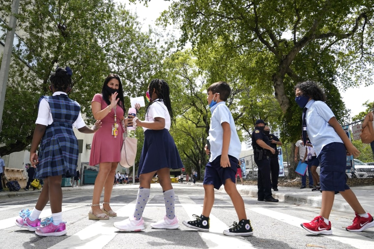 Image: A teacher greets students outside of iPrep Academy on the first day of school on Aug. 23, 2021, in Miami.