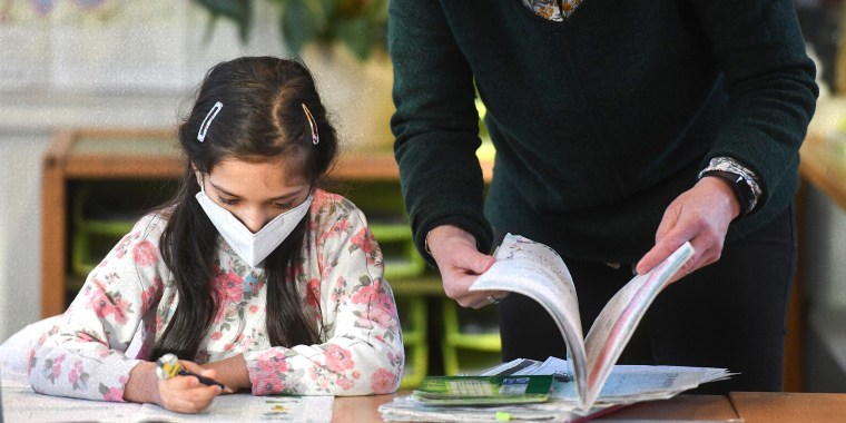 A teacher browses a book next to a second-grade pupil wearing a face mask during lessons at the Petri primary school in Dortmund, western Germany, on February 22, 2021, amid the novel coronavirus COVID-19 pandemic