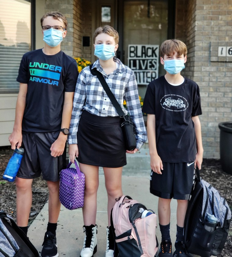 Cindy Maxwell-Ostdiek's children Luke, and Grace and Johnathan on their first day of school. They are among a minority of students who choose to wear masks in class.
