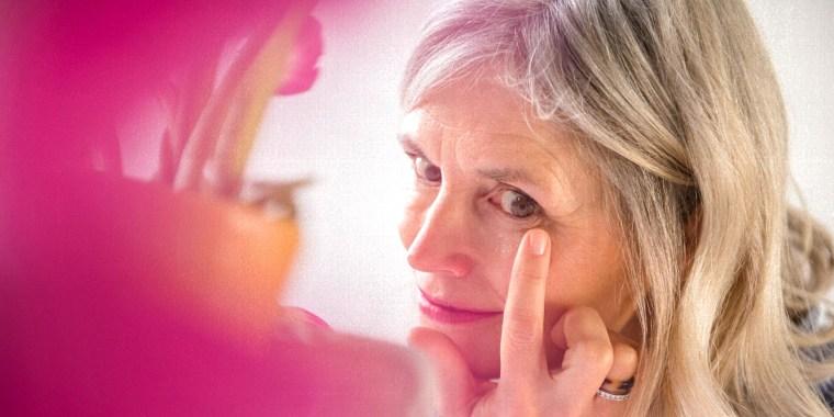 Woman applying cream to wrinkle near eye