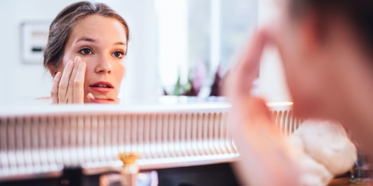Woman applying makeup in front of a big mirror.