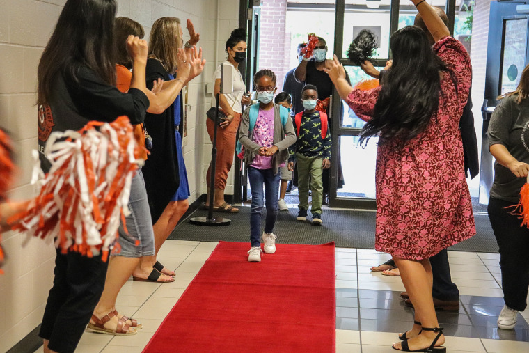 Sycamore Elementary students in Sugar Hill, Ga., walk down a red carpet laid out for them on their first day of school on Aug. 4, 2021.