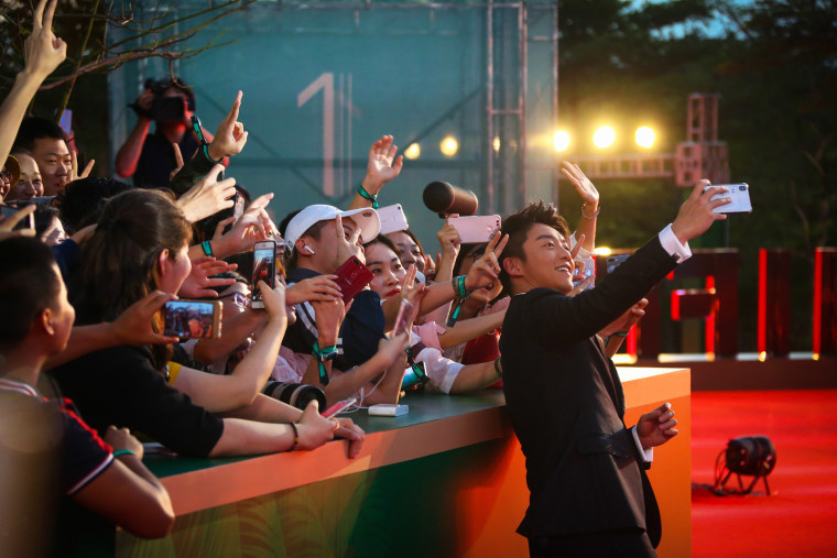 Actor Ryan Zheng Kai takes a selfie with fans on the red carpet during the opening ceremony of the 1st Hainan International Film Festival on Dec. 11, 2018, in Sanya, Hainan province, China.