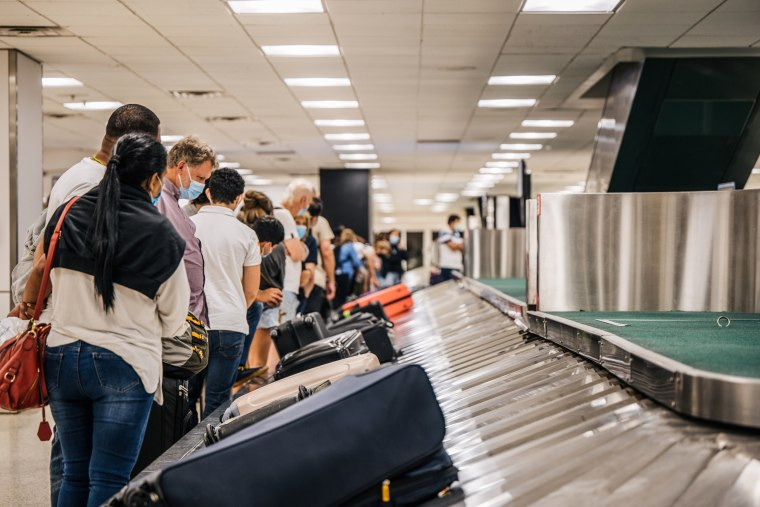 People wait for their luggage at an American Airlines baggage claim at the George Bush Intercontinental Airport on Aug. 5, 2021 in Houston, Texas.