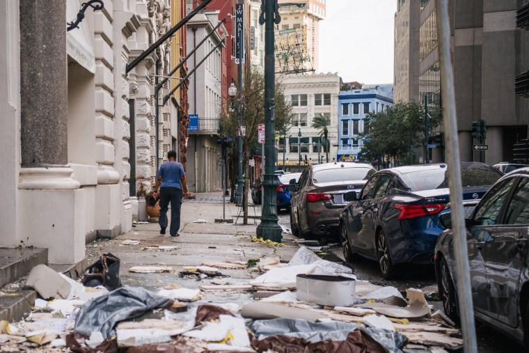 Image: A person walks past debris on the sidewalk after Hurricane Ida passed through on August 30, 2021 in New Orleans.