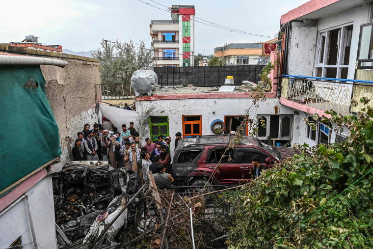 Image: Residents and family members gather next to a damaged vehicle inside a day after a U.S. drone airstrike in Kabul on Sunday.