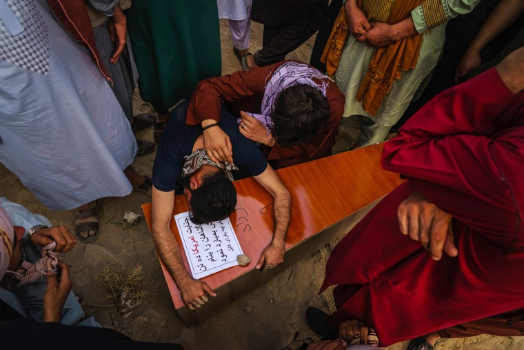 Image: A relative throws himself and weeps over Farzad's casket.