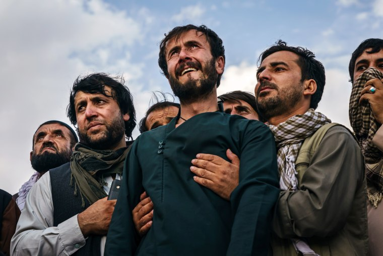 Image: Ramal Ahmadi is supported by family members during a mass funeral in Kabul on Monday.