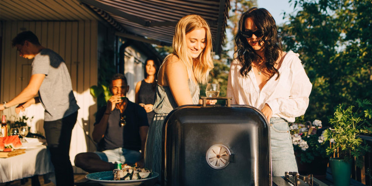 Two friends chatting while they bbq outside. Labor Day grill sales from Home Depot and more are bringing 2021 deals on Weber grills, Cuisinart grills, Victory grills, MASTER COOK grills and grilling tools.