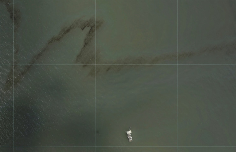 Image: A dark trail appears on the waters of the Gulf of Mexico near an oil industry platform