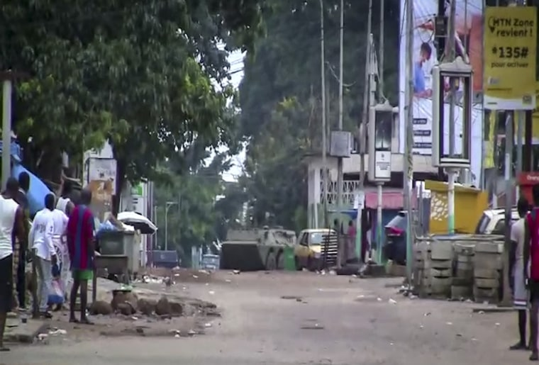 In this image made from video, residents watch as an armored personnel carrier is seen on the streets near the presidential palace in the capital Conakry, Guinea, on Sunday.