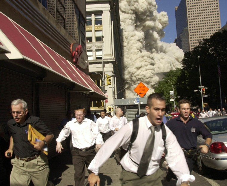 Smoke and debris fill the streets as pedestrians run for cover after the collapse of the south tower.