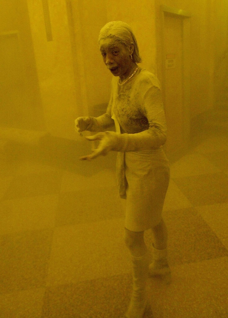 A woman covered in dust takes refuge in an office building after one of the towers collapsed.