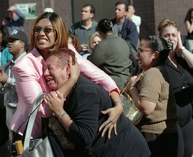Two women hold each other as they watch the World Trade Center burn.