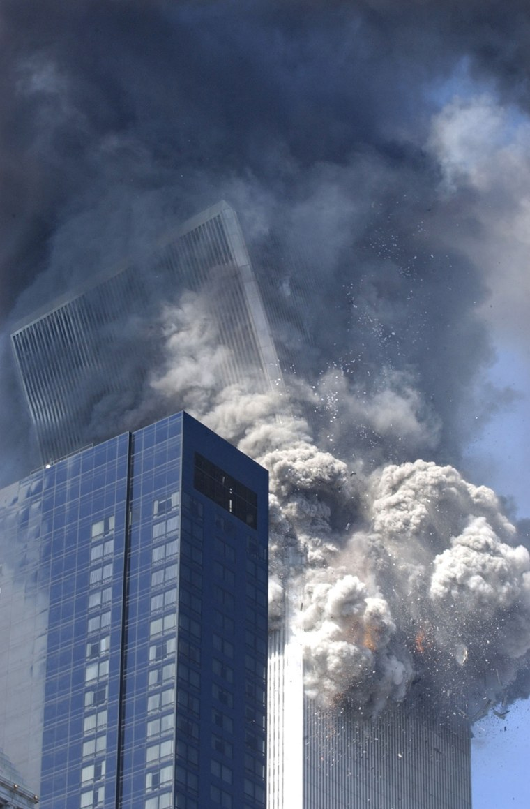 """Smoke and debris fill the air in New York City as the south tower of the World Trade Center collapses at 9:59 a.m.  \""""Clearly, not even the police and FBI who had flooded the area were worried about collapse,\"""" said George Hackett of Newsweek. \""""They wouldn't have been anywhere near to the buildings as they were. If the first building hadn't essentially fallen straight down, its crash could have killed hundreds standing, like me, a few blocks away.\"""""""