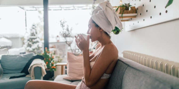 Young woman drinking first morning coffee in loft apartment, wearing a towel on her head
