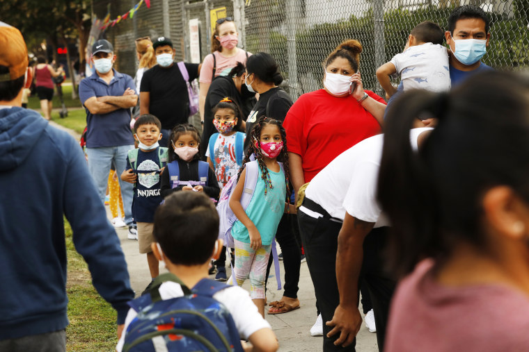 Parents and students wait in line to check pre-approved health clearances in order to enter Lankershim Elementary School in North Hollywood, Calif., on Aug. 17, 2021.