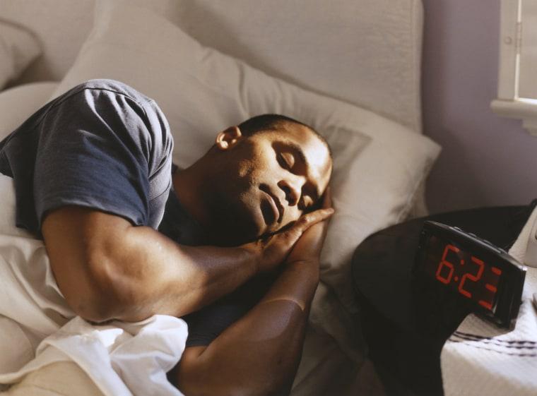 Image: Alarm clock next to man sleeping