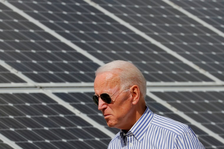 Then-candidate Joe Biden walks past solar panels while touring the Plymouth Area Renewable Energy Initiative in Plymouth, N.H., on June 4, 2019.