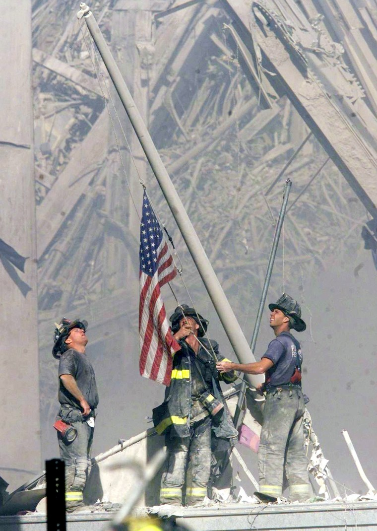 Firefighters raise a U.S. flag where the World Trade Center formerly stood on Sept. 11.