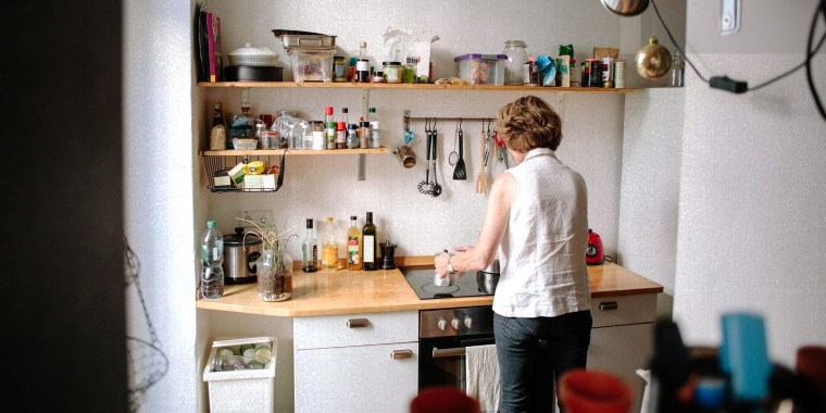 Rear view of senior woman making coffee on stove in kitchen at home