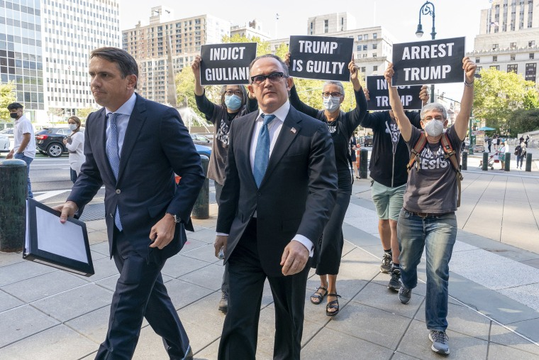 Image: Activist with Rise and Resist follow Igor Fruman, second from left, as he arrives in Federal court in Manhattan with his attorney Todd Blanche, on Sept. 10, 2021 in New York.