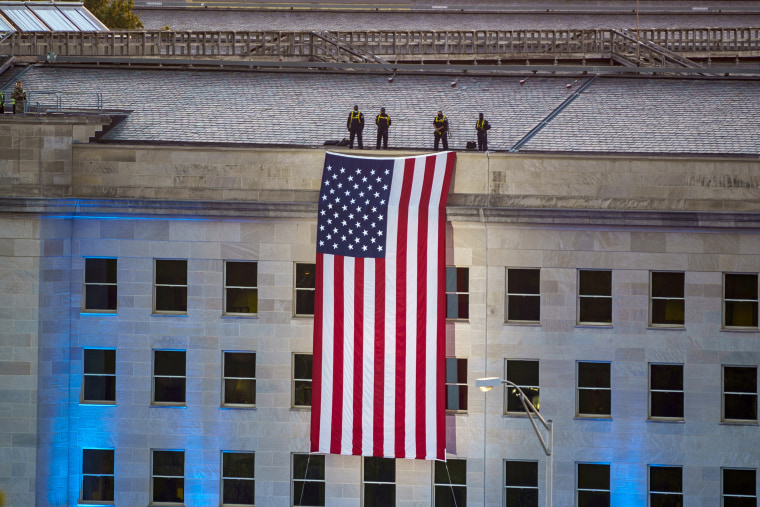 An American flag is unfurled at dawn over the Pentagon in Arlington, Va.