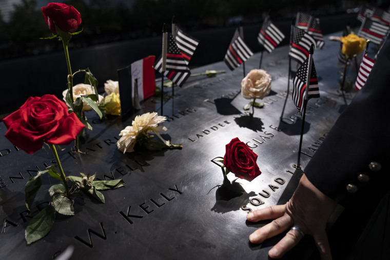 A firefighter places his hand on the name engravings on the south pool during ceremonies in New York.