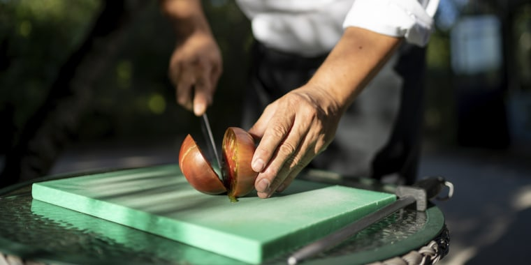 Close-up of male chef cutting tomato on table in orchard