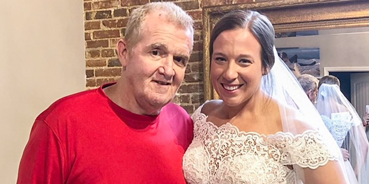 Daughter in wedding gown near dad
