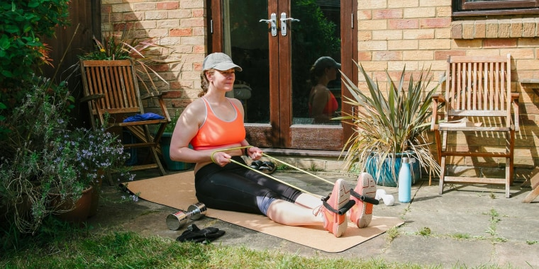 Woman sitting on a yoga may, exercising in her garden, using a resistance band