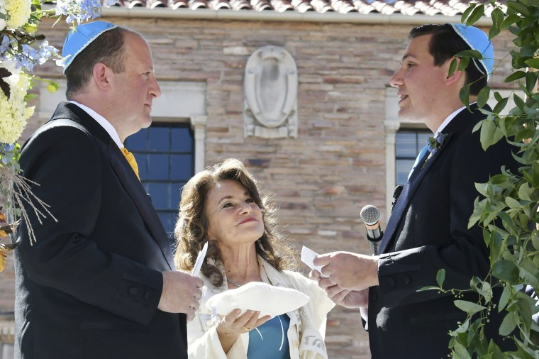 Rabbi Tirzah Firestone, center, officiates a traditional Jewish wedding ceremony for Colorado Gov. Jared Polis, left, and his partner, Marlon Reis, in Boulder, Colo. on Sept. 15, 2021.