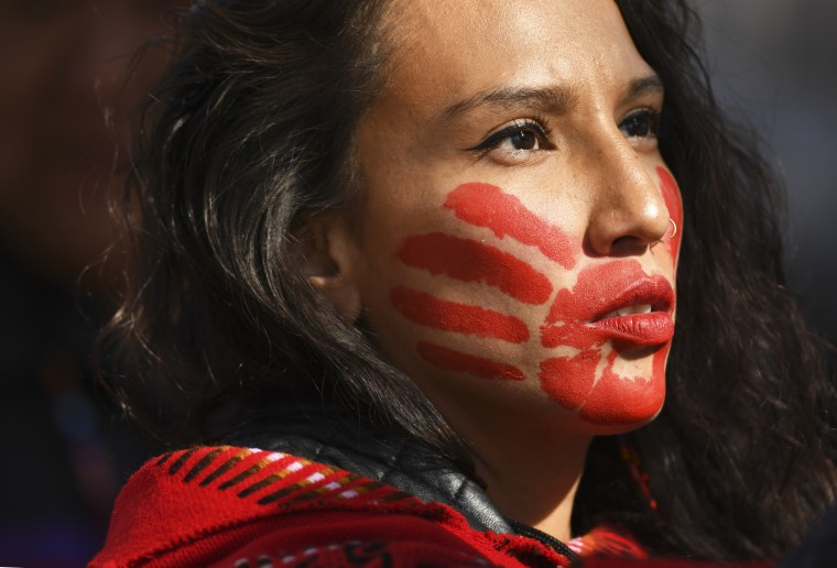 Micaela Iron Shell has painted red hands over their mouth to show solidarity for missing and murdered indigenous, Black and migrant women and children during a rally on Oct. 11, 2019, in Denver.