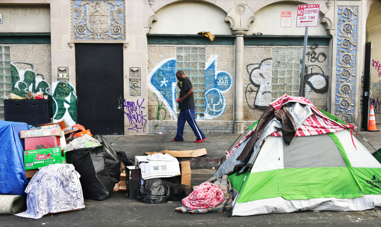 Image: A man walks past tents housing the homeless on the streets  in the Skid Row community of Los Angeles on April 26, 2021.