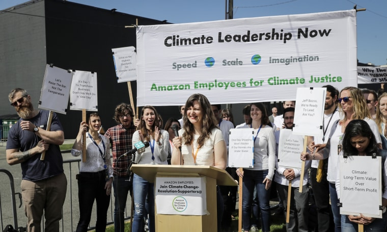 """Emily Cunningham, center, who works as a user experience designer at Amazon.com, speaks during a news conference following Amazon's annual shareholders meeting on  May 22, 2019, in Seattle held by the group \""""Amazon Employees for Climate Justice.\"""""""