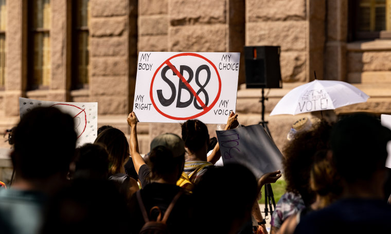 """Image: Protestors hold up a sign that has a stop sign over the text,\""""SB8\""""."""