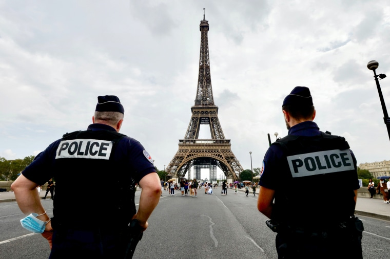French police officers stand guard in front of the Eiffel tower in Paris