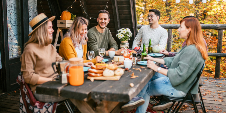 Group of smiling friends enjoys food and conversation at autumn garden party at weekend house